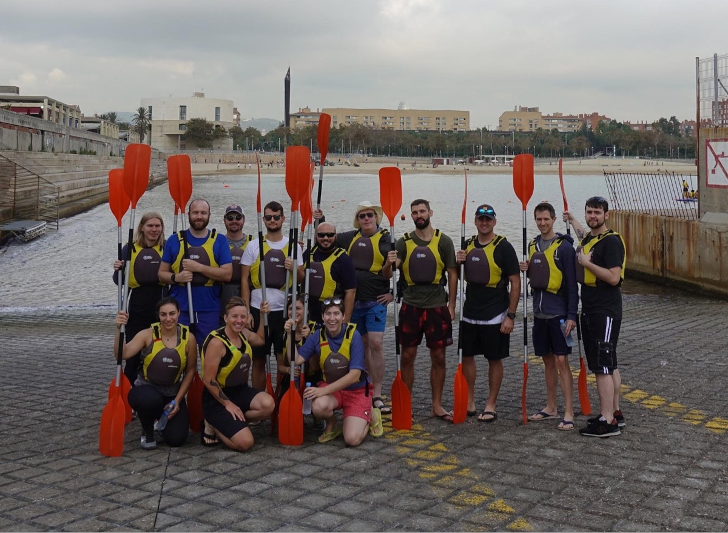 A crew of sea kayakers with their paddles during Help Scout's 2017 retreat to Barcelona, Spain